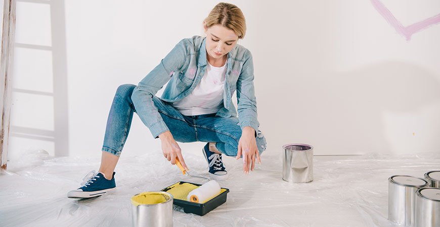 Pretty young woman putting paint roller
